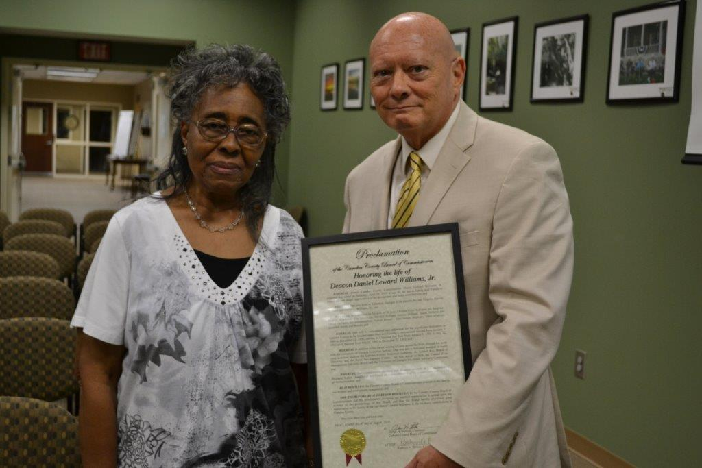 Mrs. Elvenia Waye Williams receiving proclamation from County Attorney John Myers.